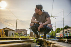 Attractive young man sitting on railroad Stock Photo