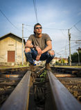 Attractive young man sitting on railroad Royalty Free Stock Photography