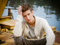 Attractive young man sitting on rusty metal Royalty Free Stock Photos