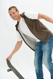 Attractive young man with skateboard Stock Images