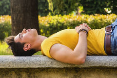 Attractive young man sleeping on stone bench Royalty Free Stock Image