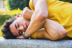 Attractive young man sleeping on stone bench Royalty Free Stock Photos