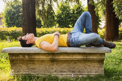 Attractive young man sleeping on stone bench. Outdoor in city park during day, full body shot Royalty Free Stock Photo