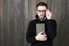 Attractive young man with a small beard in glasses and in black. Clothes with books in his hand pressed to his chest squinting looking at the camera against the Stock Photo