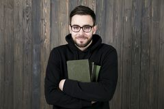Attractive young man with a small beard in glasses and in black. Clothes with books in arms crossed on his chest smiling looking at the camera on a wooden wall Stock Photo