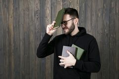 An attractive young man with a small beard in glasses and black. Clothes with books in one hand, pressed his other hand with a book to his forehead and closed Royalty Free Stock Photos