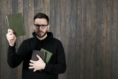 An attractive young man with a small beard wearing glasses and w. Earing black clothes with books in his hand looks closely at the camera, raising his other hand Royalty Free Stock Photography