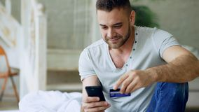 Attractive young man with smartphone and credit card shopping on the internet sit on bed at home. Attractive young man with smartphone and credit card shopping stock photography