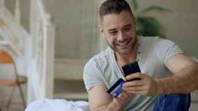 Attractive young man with smartphone and credit card shopping on the internet sit on bed at home