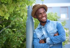 Attractive young man smiling with arms crossed Stock Images