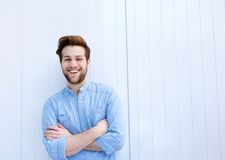 Attractive young man smiling with arms crossed Royalty Free Stock Image