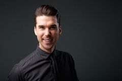 Attractive young man smiling in black shirt and tie Stock Image