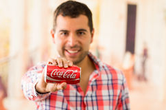 Attractive young man smiling holding a Coca-Cola. QUITO, ECUADOR - AUGUST 3, 2015: Attractive young man smiling holding a Coca-Cola can Royalty Free Stock Photo