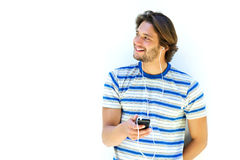 Attractive young man smiling and holding mp3 player Royalty Free Stock Images