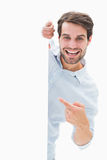 Attractive young man smiling and holding poster Royalty Free Stock Photography