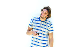 Attractive young man smiling and listening to music Stock Photography