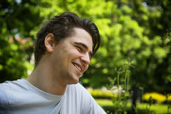 Attractive young man smiling in nature environment Stock Image