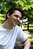 Attractive young man smiling in nature environment Stock Photo