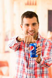 Attractive young man smiling opening a Pepsi Cola. QUITO, ECUADOR - AUGUST 3, 2015: Attractive young man smiling opening a Pepsi Cola can Royalty Free Stock Image