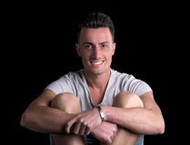 Attractive young man smiling, sitting, arms around knees Royalty Free Stock Photos
