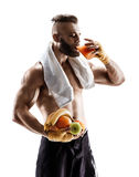 Attractive young man in sports wear with towel on his shoulders hold fresh fruits and drink juice Royalty Free Stock Images
