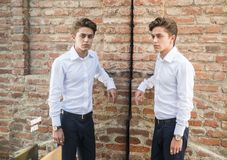 Attractive young man standing against brick wall. And big mirror, looking at camera through the reflection. Half body shot royalty free stock photography