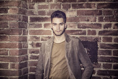Attractive young man standing against brick wall. Looking at camera Royalty Free Stock Photo