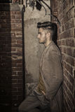 Attractive young man standing against brick wall. Profile view of attractive young man standing against brick wall, looking away to a side Royalty Free Stock Photos