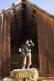 Attractive Young Man Standing on a Bale of Hay Royalty Free Stock Images