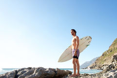 Attractive young man standing on beach carrying surfboard Royalty Free Stock Photography
