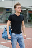 Attractive young man standing in city environment, with backsack Royalty Free Stock Photos