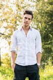 Attractive young man standing in a forest Stock Photos