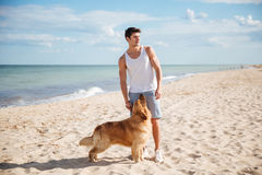 Attractive young man standing with his dog on the beach Royalty Free Stock Photography