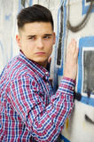 Attractive  young man standing next to colorful graffiti Stock Image