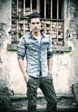 Attractive young man standing outdoor in front of abandoned house Stock Photography