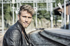 Attractive young man standing on railroad tracks. Attractive blond young man standing on railroad tracks, wearing only black leather jacket, looking at camera Stock Photo