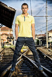 Attractive young man standing on railroad Stock Image