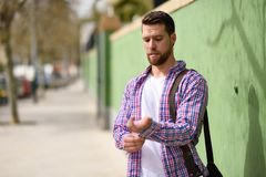 Attractive young man standing in urban background. Lifestyle concept. Attractive young man standing in urban background. Guy wearing casual clothes. Lifestyle stock photography