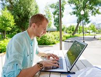 Attractive young man student using laptop outside stock photo