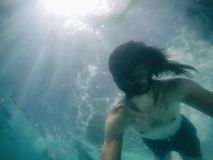 Attractive young man submerged in pool with long hair. Summer Stock Photography