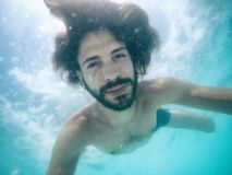 Attractive young man submerged in pool looking at camera. Summer Royalty Free Stock Images