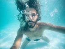 Attractive young man submerged in pool looking at camera. Summer Stock Photography