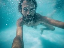 Attractive young man submerged in pool looking at camera. Summer Stock Photo