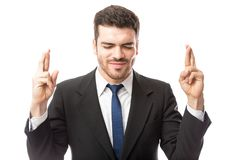 Businessman wishing for luck. Attractive young man in a suit with his fingers crossed wishing for good luck in a studio Stock Images