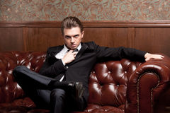 Attractive young man in a suit sitting on couch Stock Images