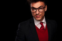 Attractive young man in suit, wearing tie. Close portrait of attractive young man in suit, wearing tie and glasses, looking at the camera in dark studio Royalty Free Stock Image