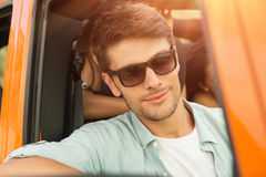 Attractive young man in sunglasses sitting on a front seat. Inside a car Stock Photography