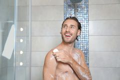 Attractive young man taking shower with soap. In bathroom royalty free stock images