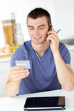 Attractive young man talking on phone holding card Stock Photo