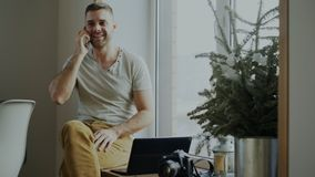 Attractive young man talking phone sitting on windowsill with laptop and camera at home. Indoors Stock Photos